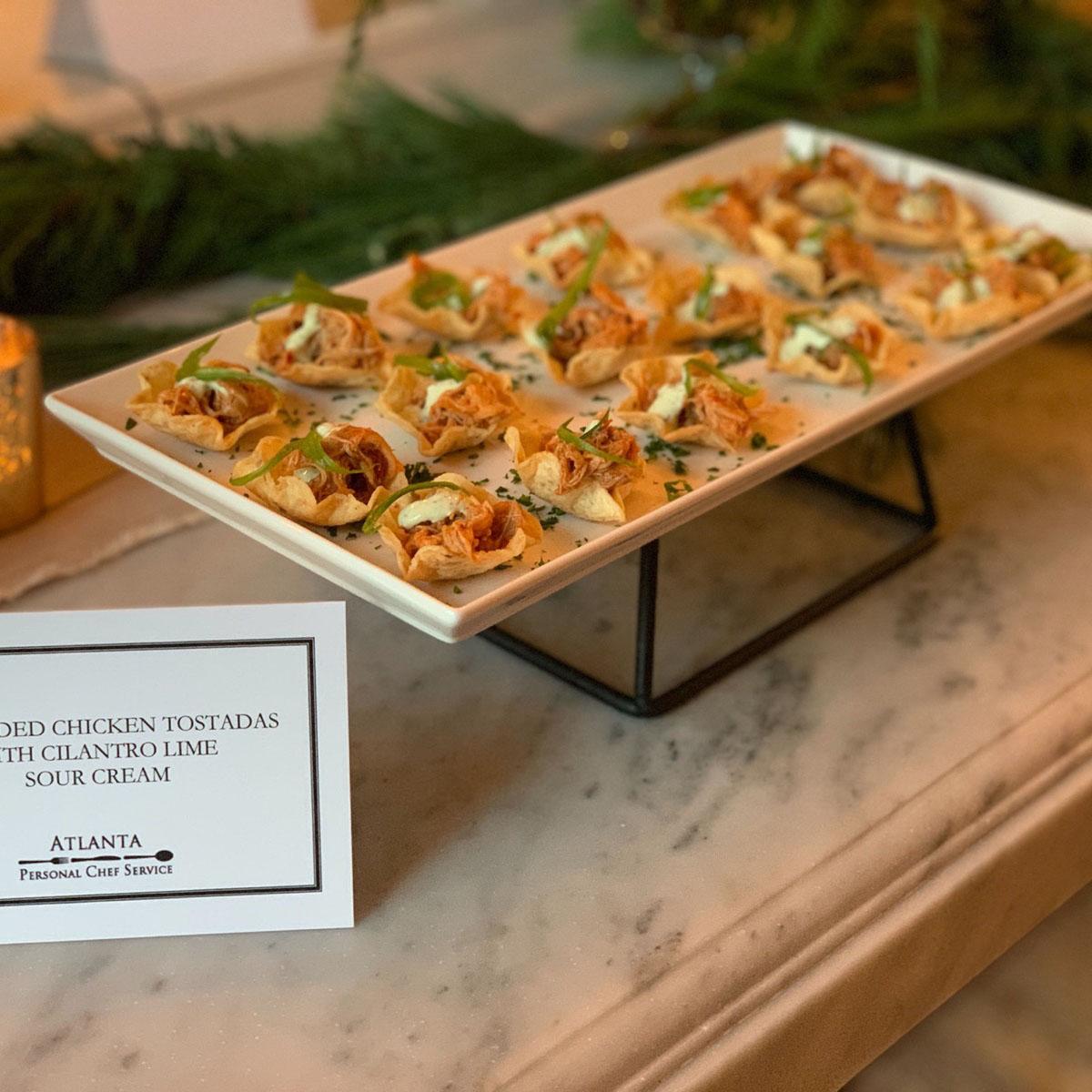 Elevated reception food consisting of chicken tinga tostadas with cilantro crema and custom printed menu description cards