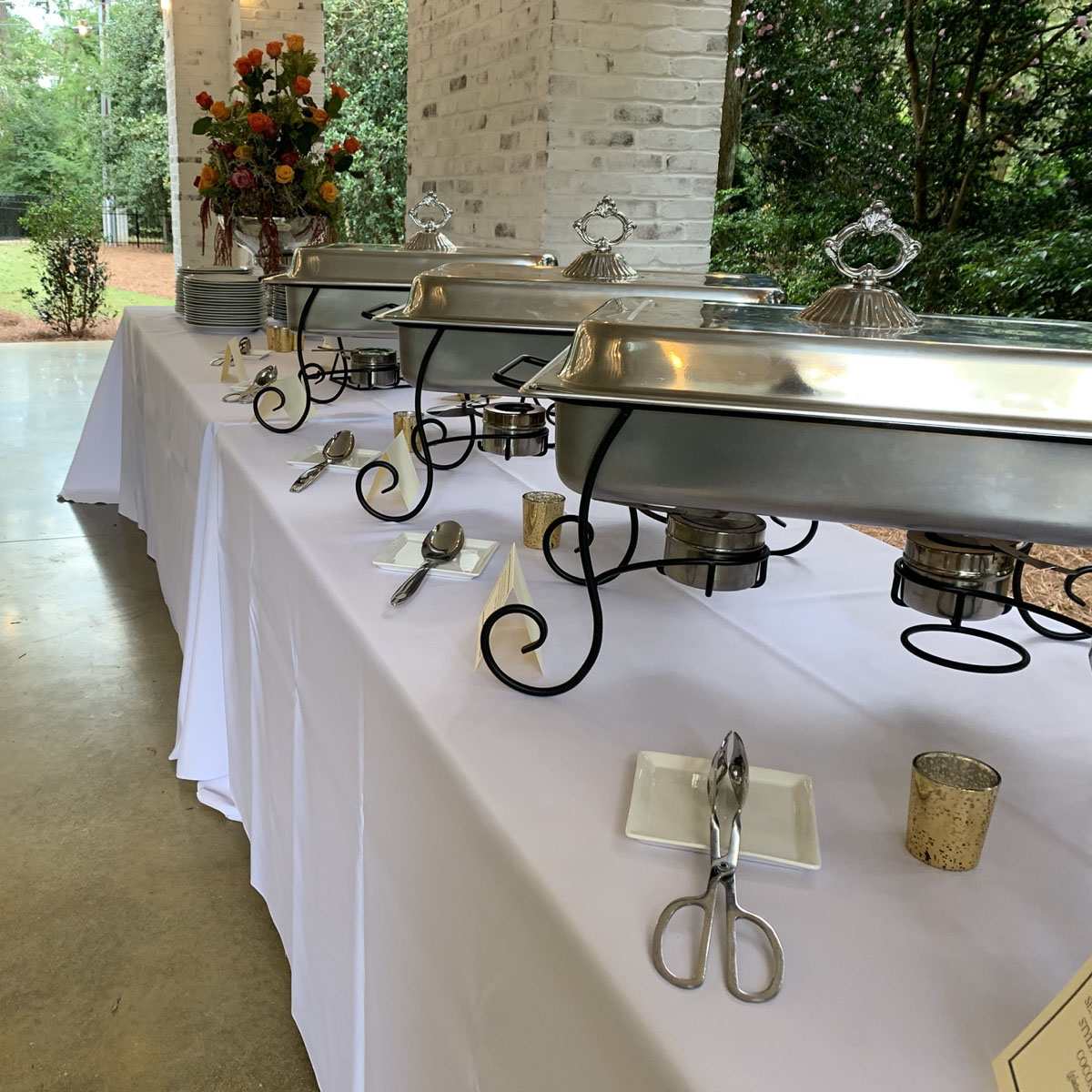 Buffet style dinner set up with chafing dishes, white tablecloths, tealight candles and floral arrangements