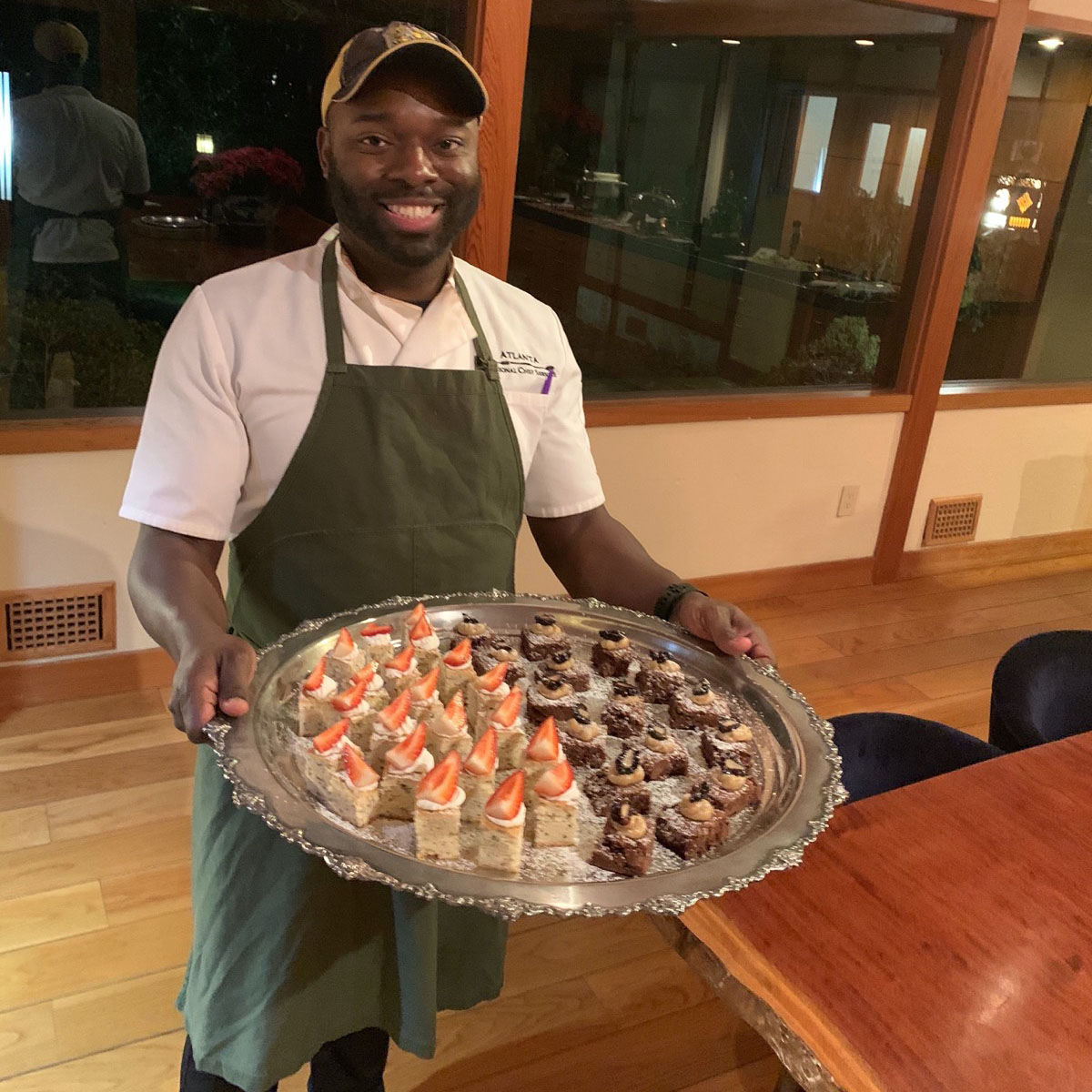 Executive personal chef Tai holding a platter of reception style desserts consisting of strawberry shortcake and fudge brownie bites