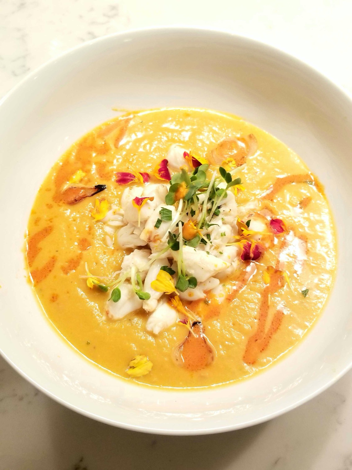 Fresh homemade crab and acorn squash bisque with edible flowers