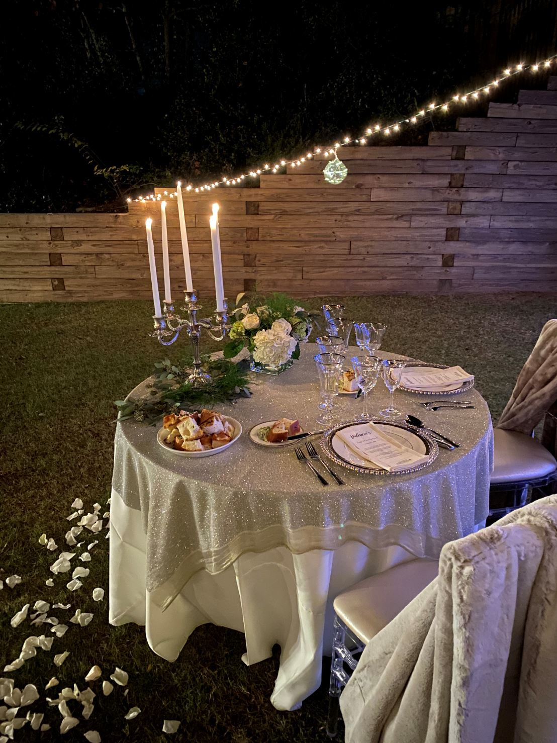 Fancy private party table setting with white rollups, chargers, custom menu and floral arrangements